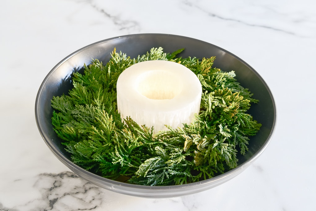 black bowl centerpiece with Christmas greenery and white candle holder in the center