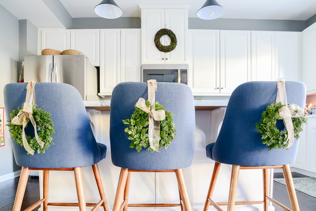 blue kitchen counter stools with mini green christmas wreaths on the back