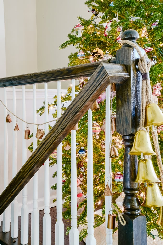 handmade noah bell garland hanging on staircase next to Christmas tree
