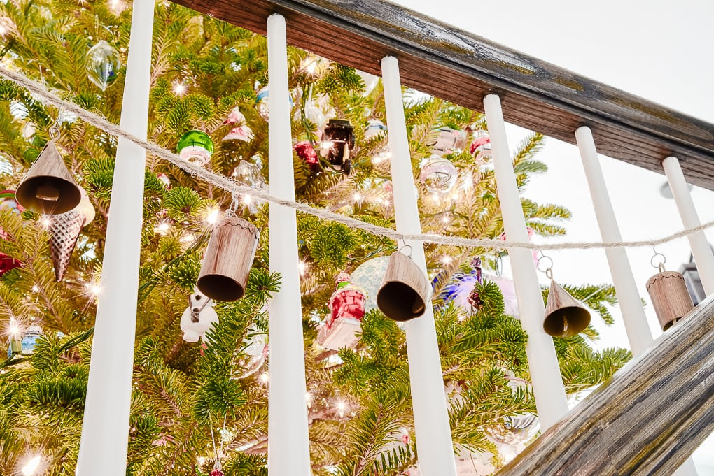handmade noah bell garland hanging on staircase leading up to Christmas tree