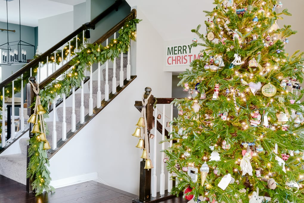 pine and eucalyptus Christmas garland with hanging gold bells on staircase and fresh Christmas tree