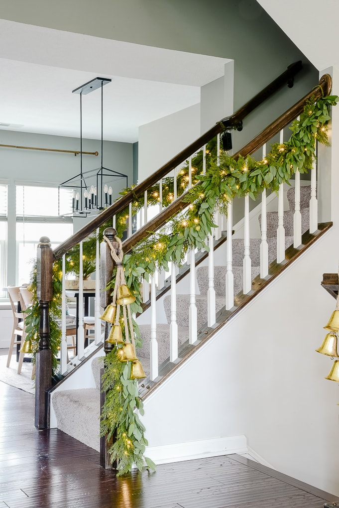 pine and eucalyptus Christmas garland with hanging gold bells on staircase