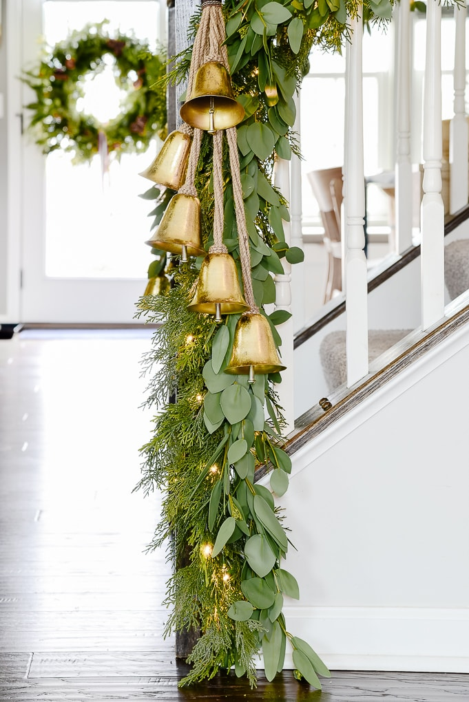 pine and eucalyptus Christmas garland with hanging gold bells on staircase lower section