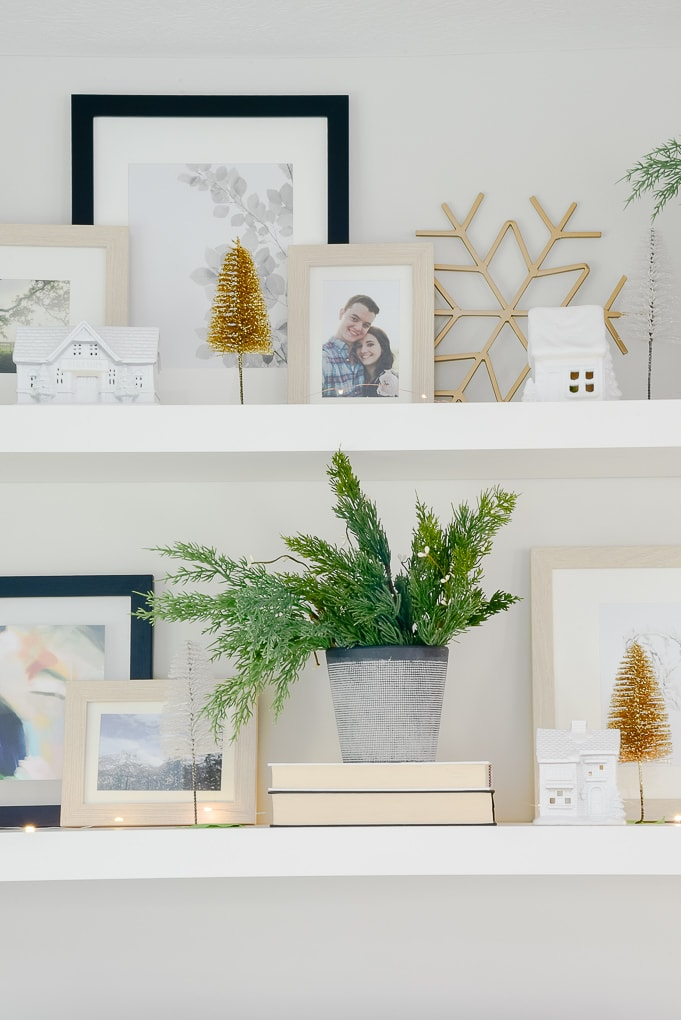 vase of faux Christmas greenery and white Christmas village houses with gold and white bottle brush trees on styled shelves