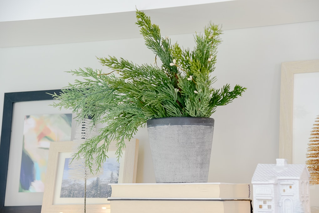 vase of faux Christmas greenery on styled shelves