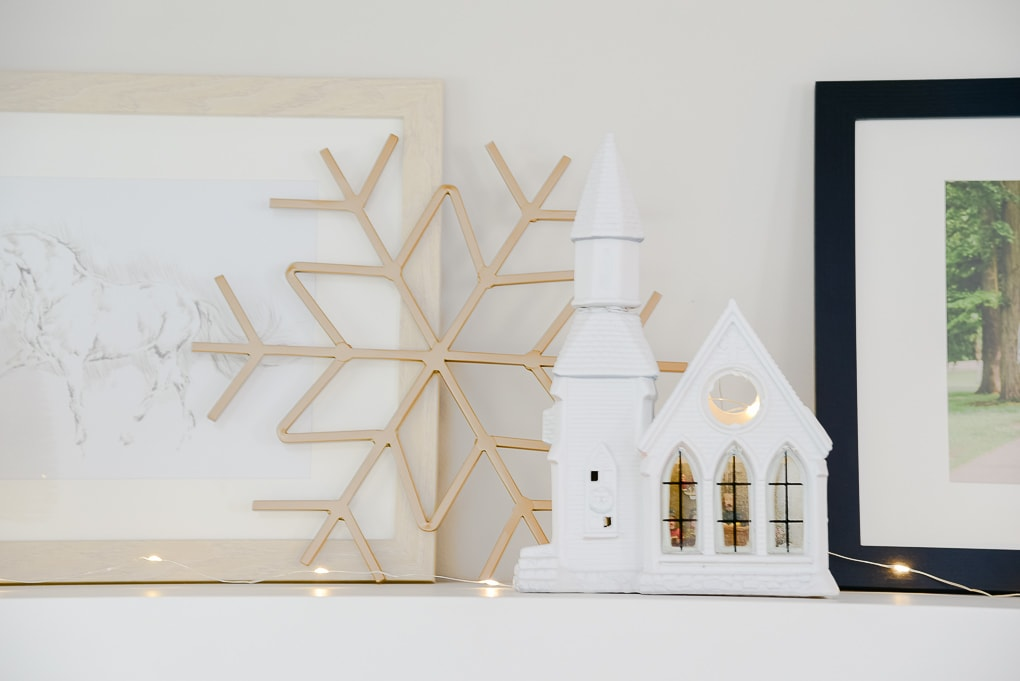 white Christmas village church and gold metal snowflake figurine on styled shelves