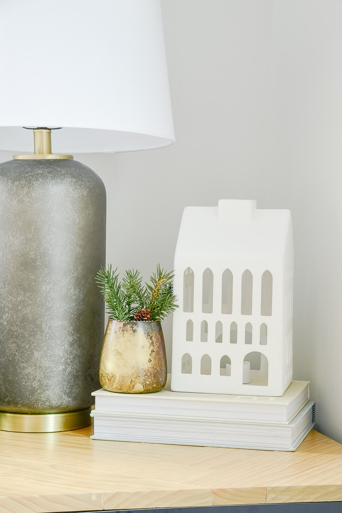 white ceramic Christmas house on end table stack of books and gold vase with greenery next to it