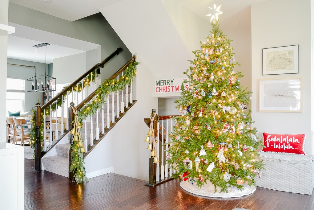 fresh Christmas tree decorated in modern classic living room with family ornaments and greenery garland on staircase