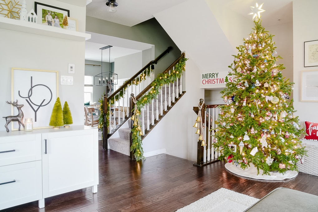 modern classic living room decorated for Christmas with garland on the staircase and fresh Christmas tree in the corner