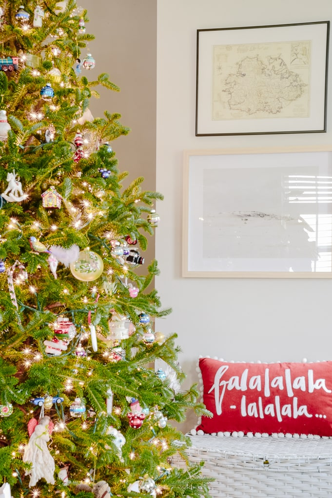 fresh Christmas tree decorated with family ornaments in front of modern artwork on the wall and a Christmas pillow