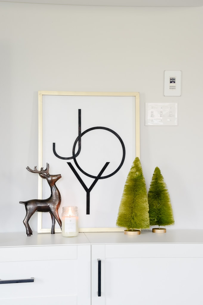 Modern Joy Christmas sign on media center with reindeer figurine and green bottle brush trees and candle