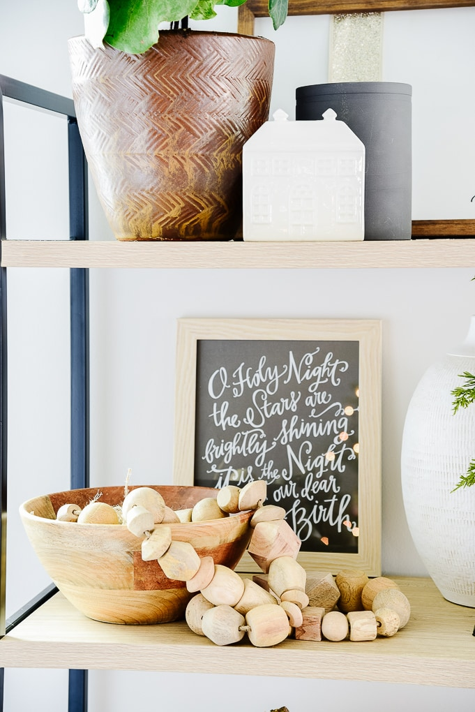 Studio McGee wooden garland from target in wooden bowl on shelf with O Holy Night print framed in the background from Lindsay Letters