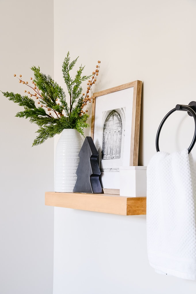 wooden shelf in master bathroom with white vase christmas greenery and black modern tree figurine