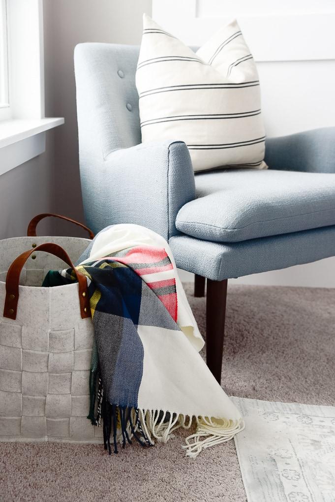 plaid tartan christmas throw blanket inside of a felt basket next to a blue accent chair