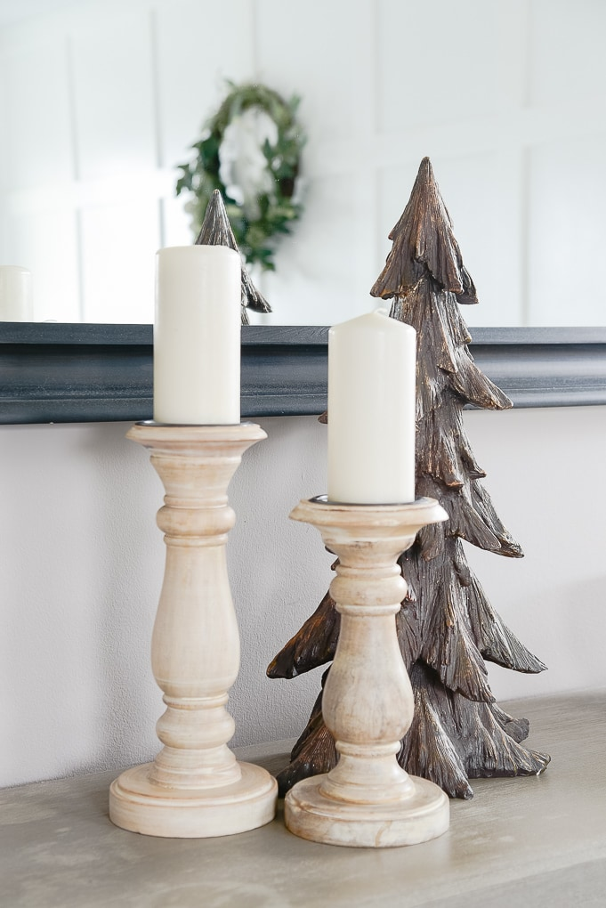 natural wooden pillar candle holders on bookshelf with brown wooden christmas tree figurine