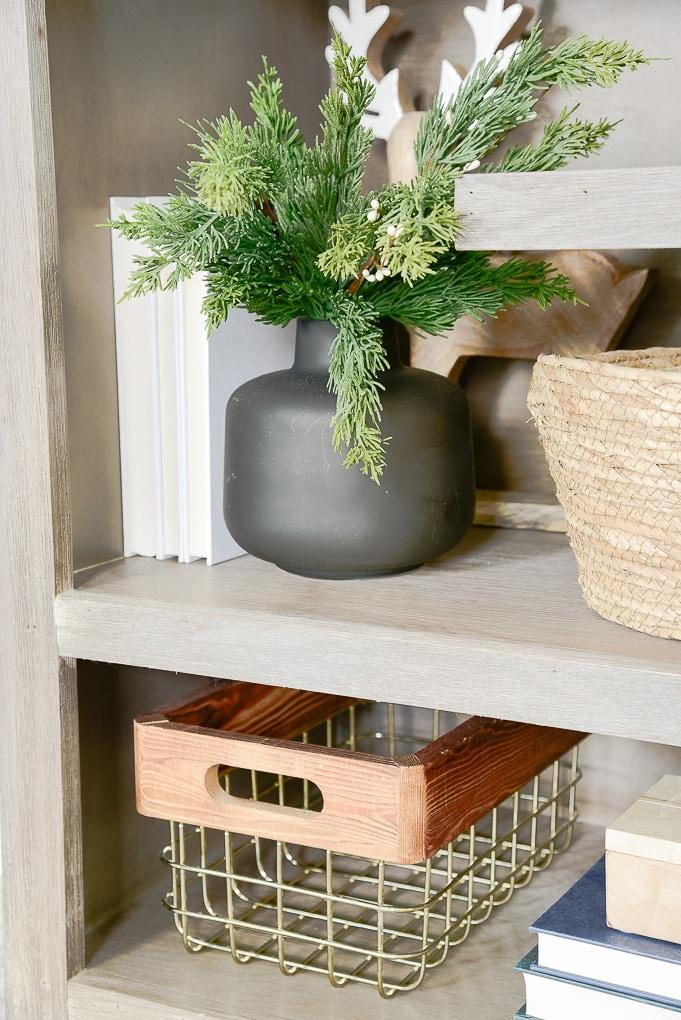 short black vase on bookshelf with faux christmas greenery