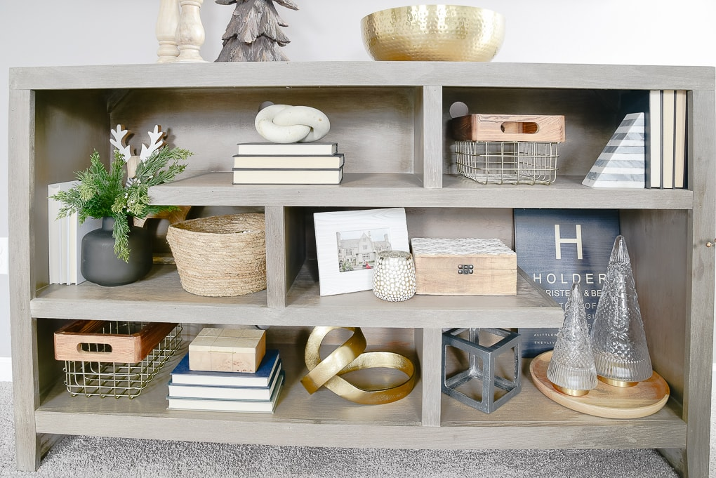 gray bookshelves decorated and styled for Christmas with gold and wooden accents