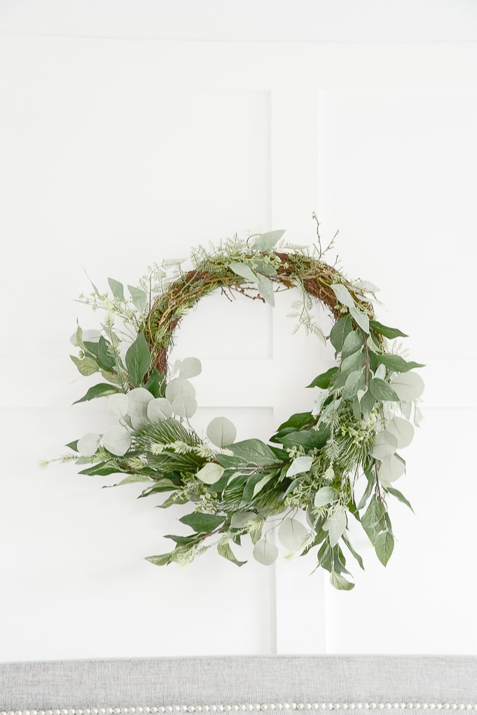modern greenery and eucalyptus wreath against white board and batten wall