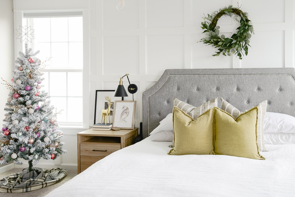 master bedroom bed and christmas tree decorated for the holidays