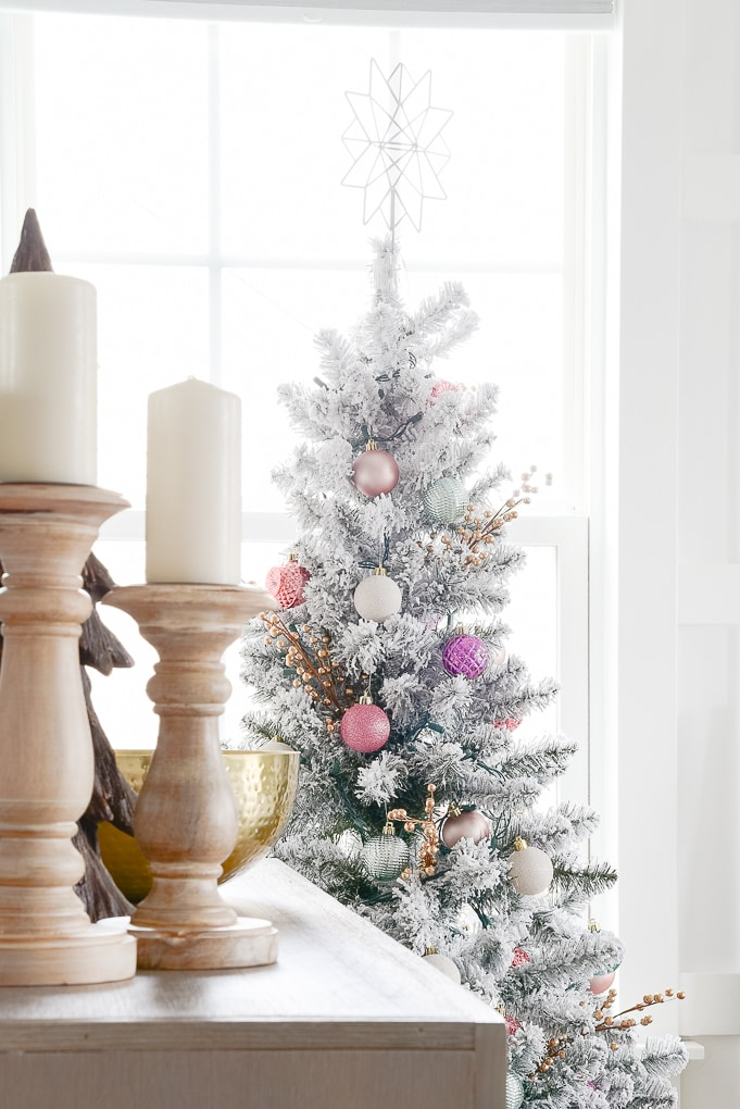 natural wooden pillar candle holders on bookshelf with flocked decorated christmas tree in the background