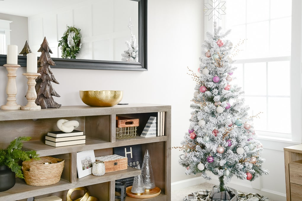 flocked decorated christmas tree next to styled gray bookshelf in master bedroom