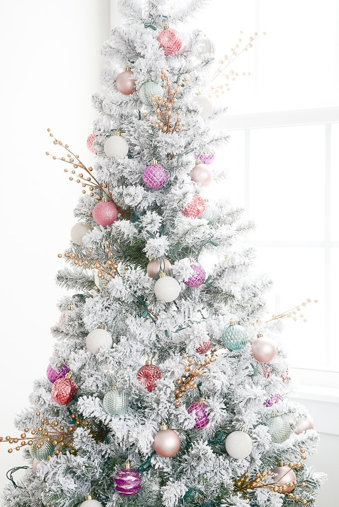 colorful ornaments on flocked decorated christmas tree