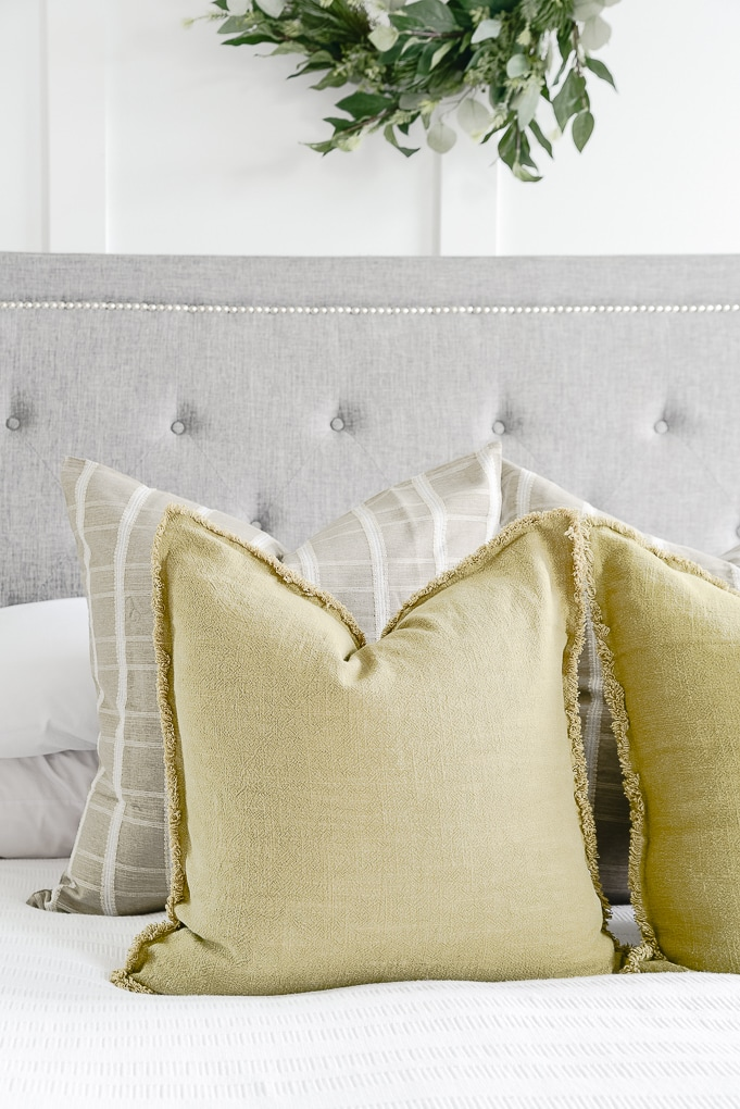 olive green throw pillows on white bedding in master bedroom