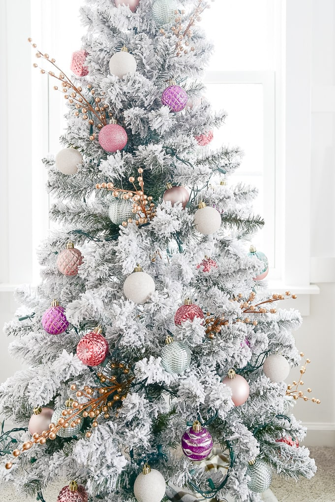 close up of flocked decorated christmas tree with colorful ornaments