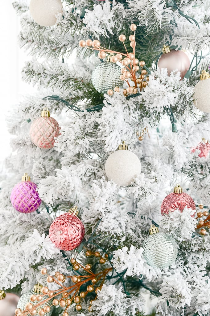 colorful pink and purple ornaments on flocked christmas tree
