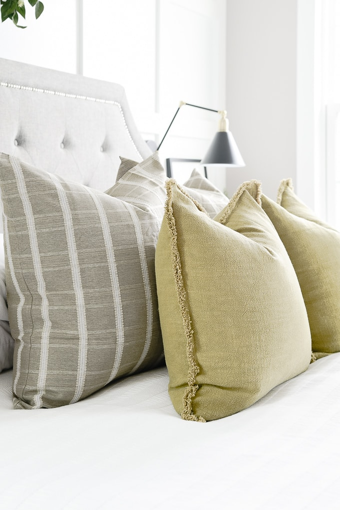 olive throw pillows layered with green windowpane pattern throw pillows on bed in master bedroom