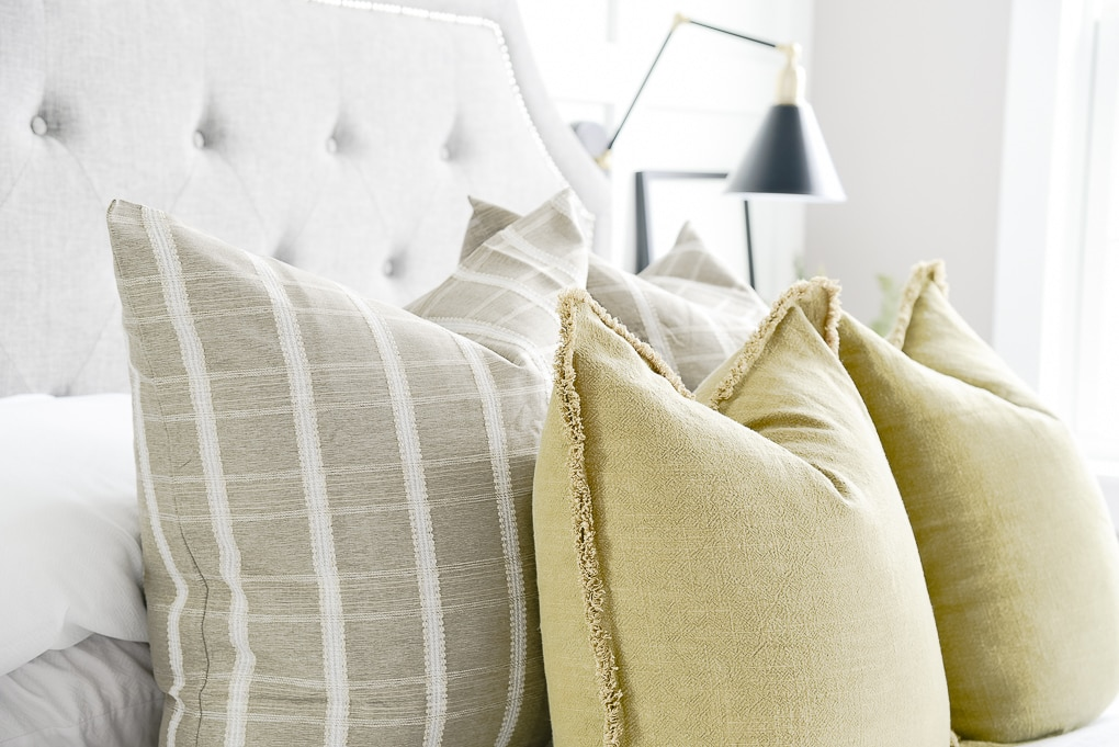 close up of olive throw pillows layered with green windowpane pattern throw pillows on bed in master bedroom