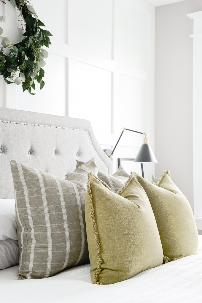 olive throw pillows layered with green windowpane pattern throw pillows on bed in master bedroom with eucalyptus wreath above the bed