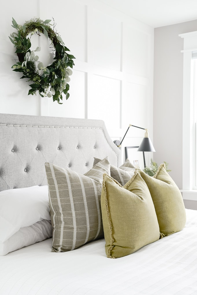 olive throw pillows layered with green windowpane pattern throw pillows on bed in master bedroom with eucalyptus wreath on the wall above the bed