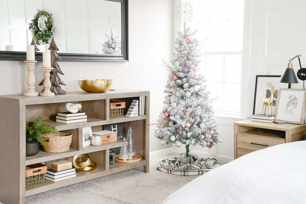 flocked decorated christmas tree in the corner of a master bedroom