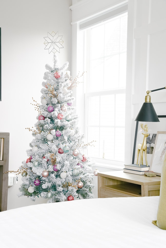 flocked christmas tree decorated with plaid tree skirt and colorful ornaments