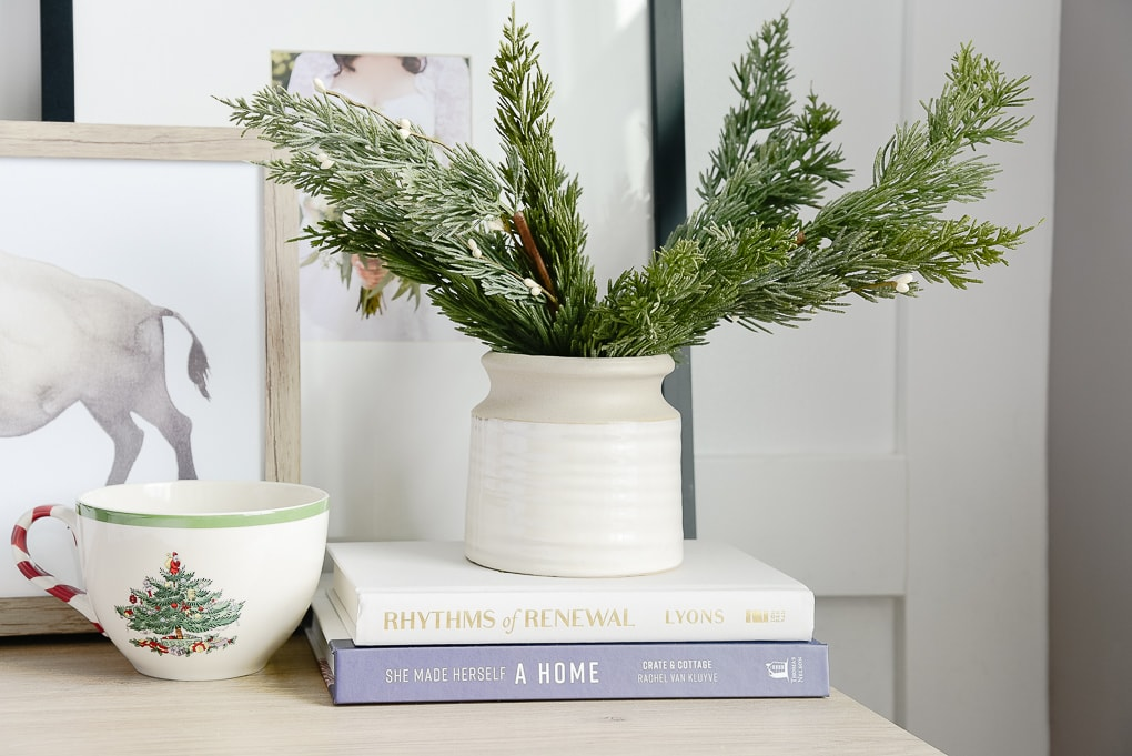 faux christmas greenery inside of a mcgee and co vase and spode christmas mug on nightstand
