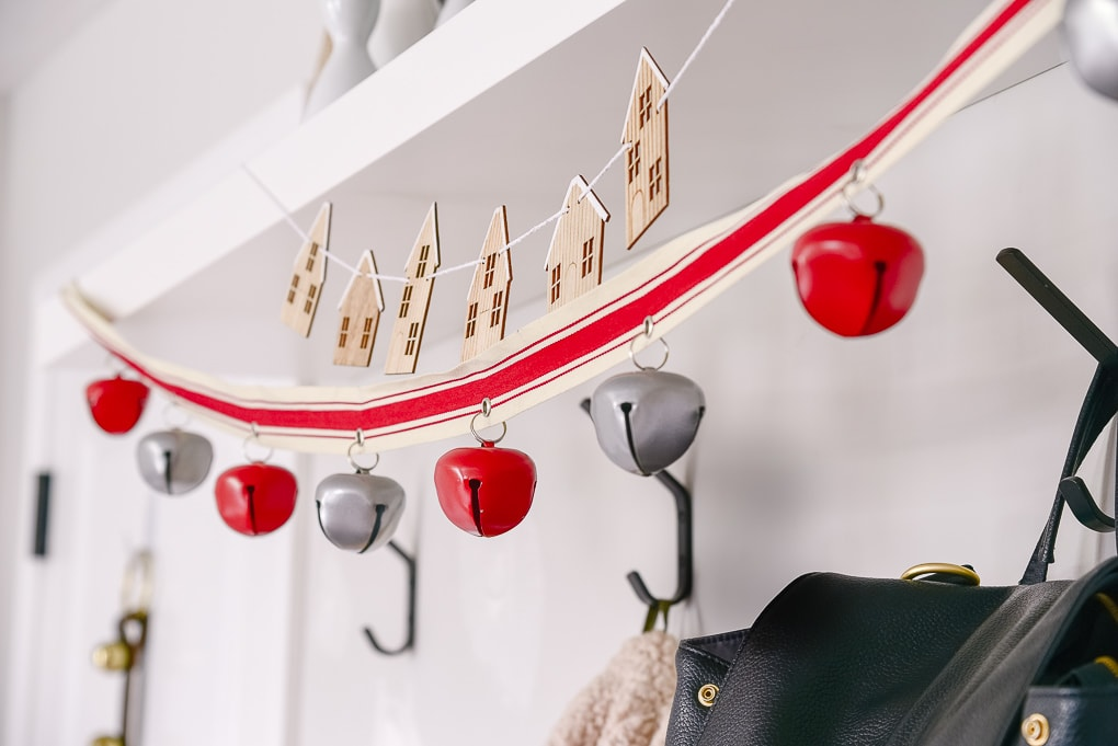 close up of red bell garland hung in a mudroom for christmas