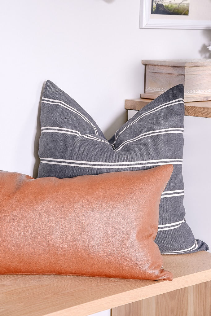 dark gray pillow and leather lumbar pillow on a bench