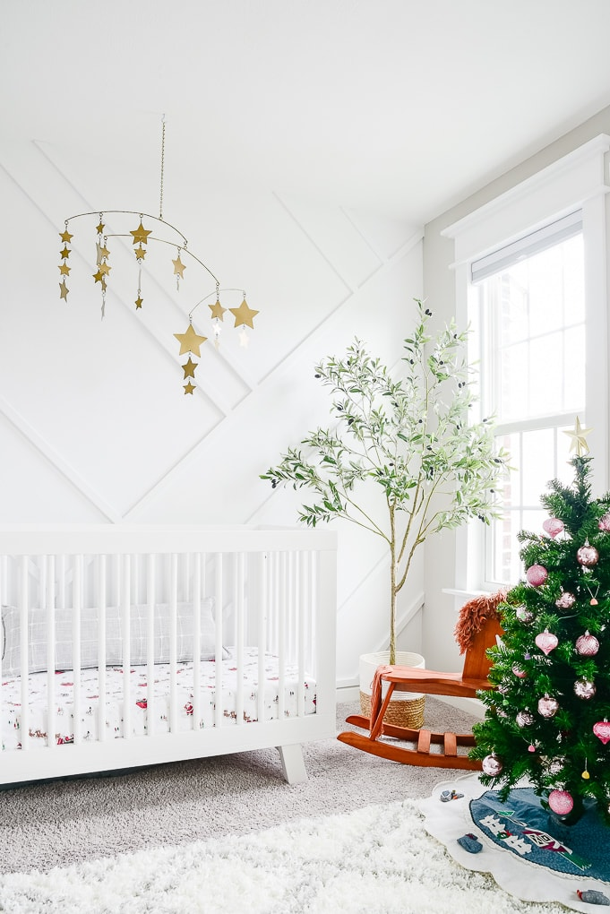 baby nursery white decorated with a kids christmas tree for the holidays