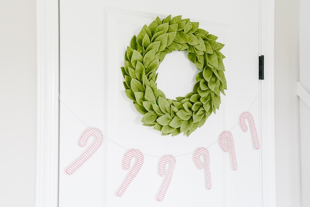 felt greenery wreath on a door above a candy cane christmas garland