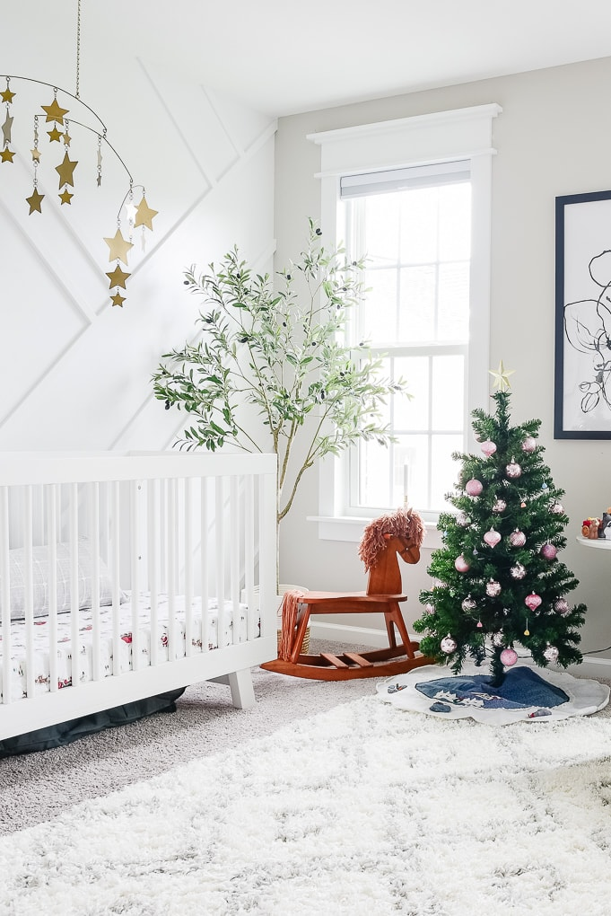 bright white nursery decorated for Christmas with a small multicolor tree