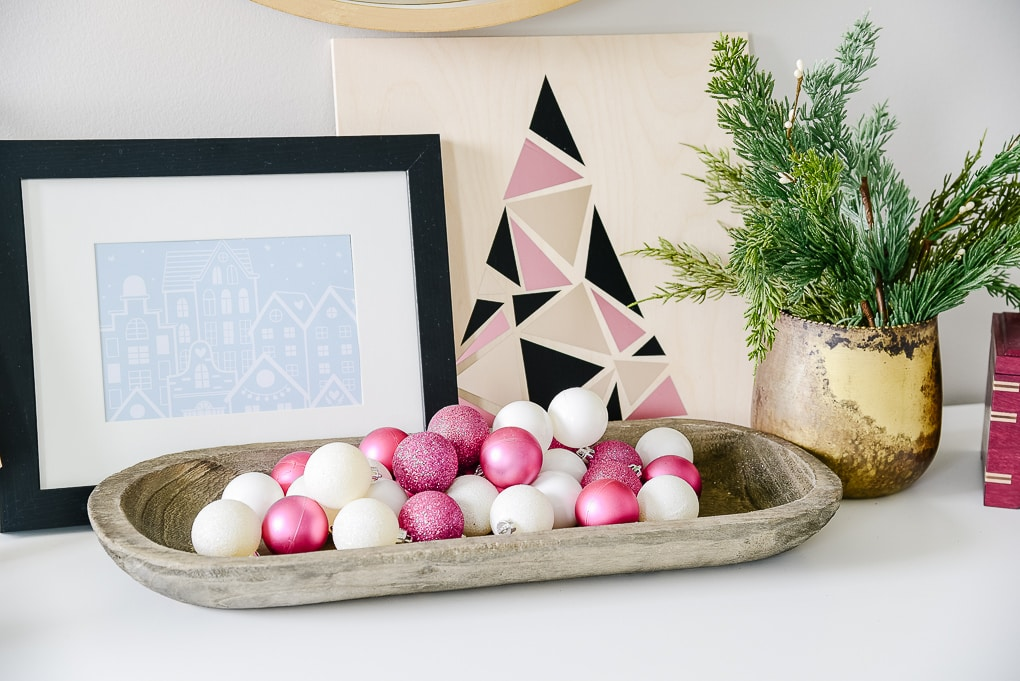 pink and white ornaments in gray tray with christmas artwork behind it