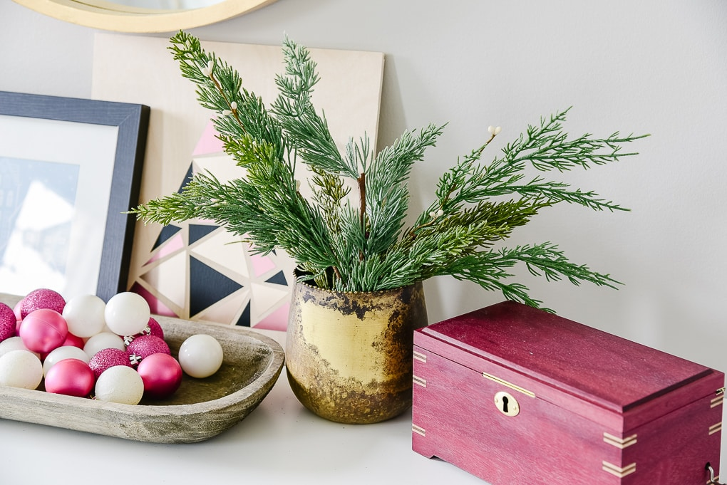 gold vase with christmas greenery on dresser