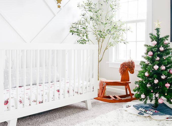 white nursery decorated for christmas with a small tree