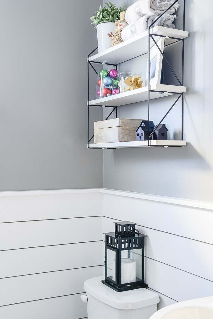 shiplap powder room decorated for Christmas with black lantern