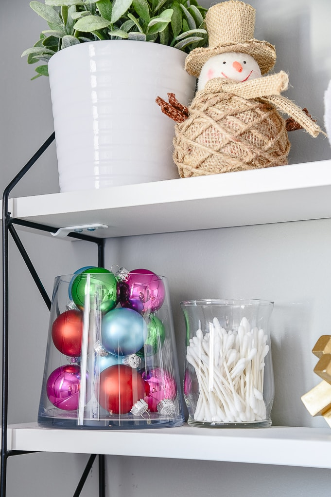 styled shelves in powder room decorated for Christmas with colorful ornaments in a glass jar