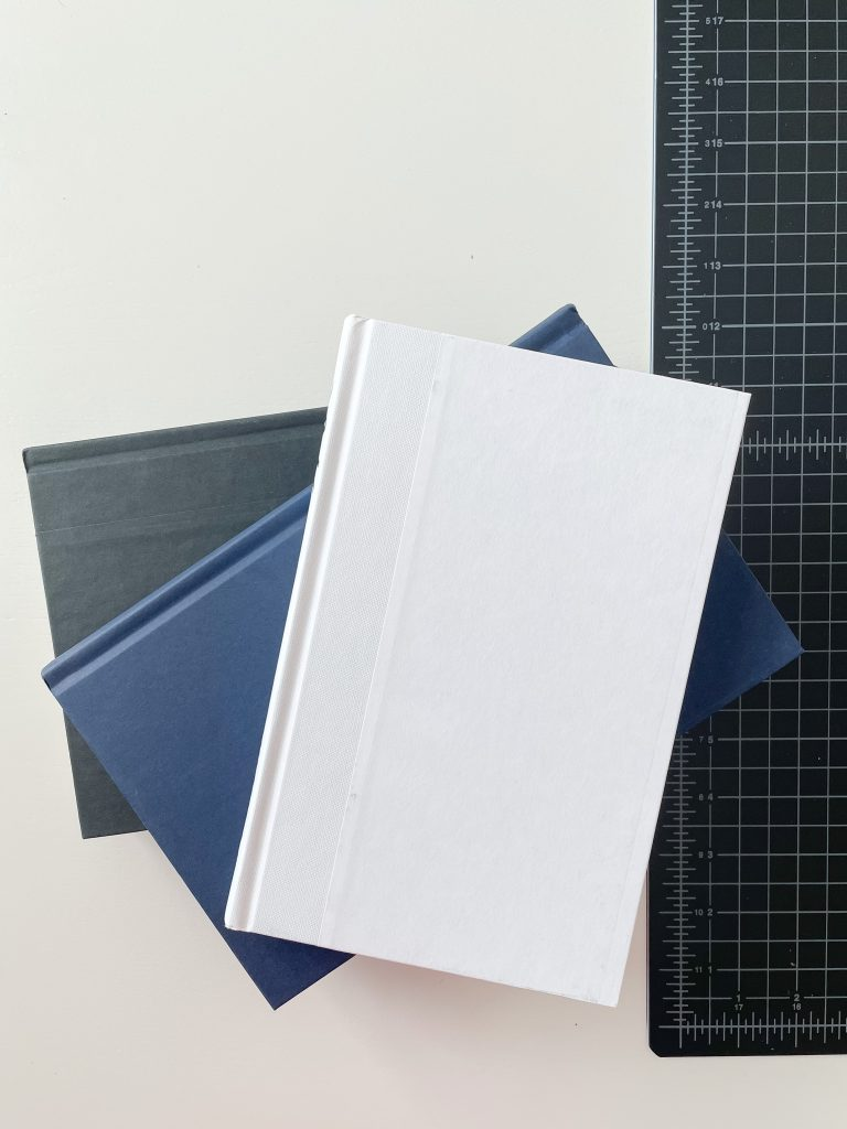 three hardcover books with plain covers in black blue and white on a table