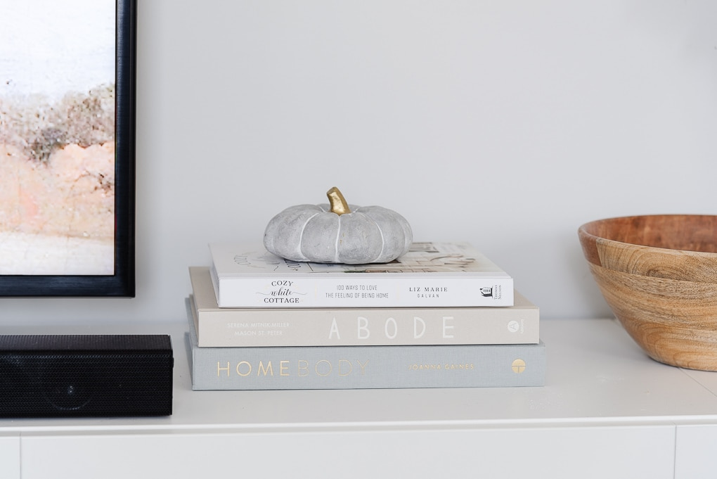 neutral home decor books stacked with a decorative pumpkin on top