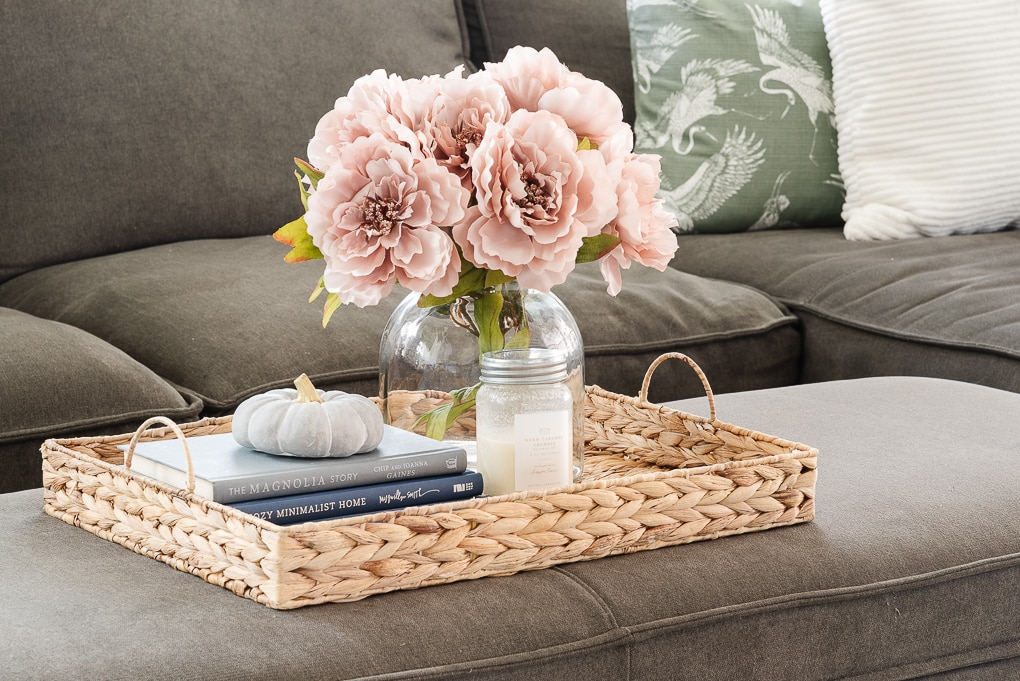 books inside of a woven basket tray on a living room ottoman with home decor