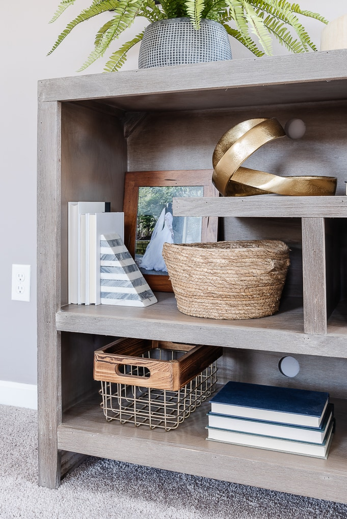 neutral decorative books on gray shelves with other home decor interspersed